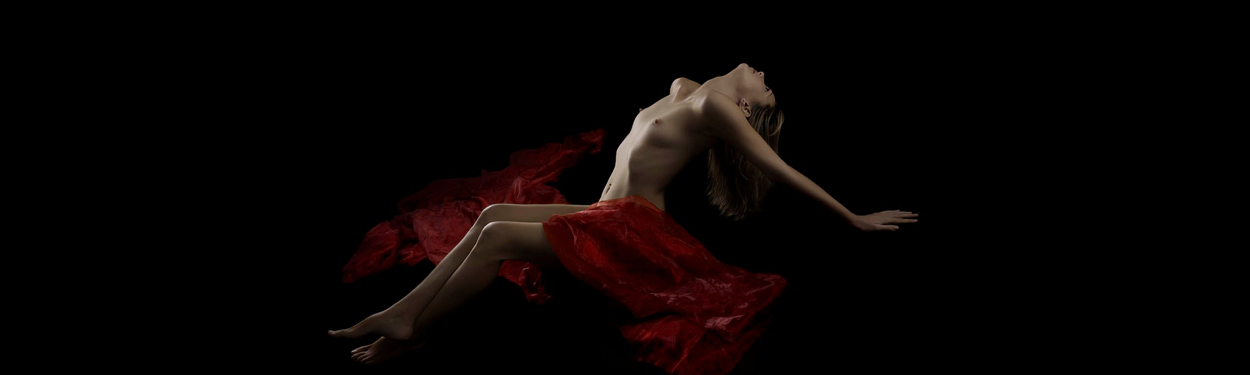 Nude woman draped in red fabric
